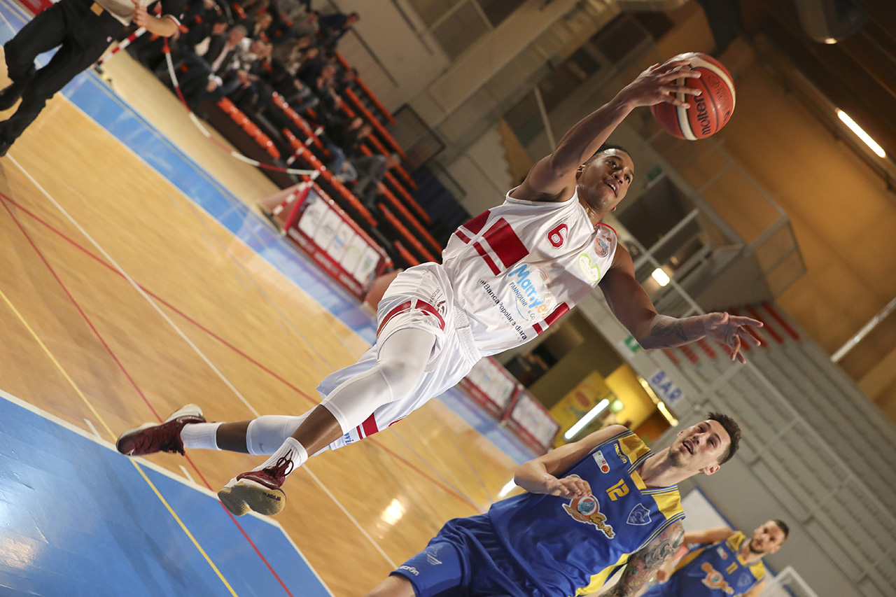 Fotografia sportiva. Un giocatore di basket mentre fa canestro durante una partita. Foto di Luca Finessi.