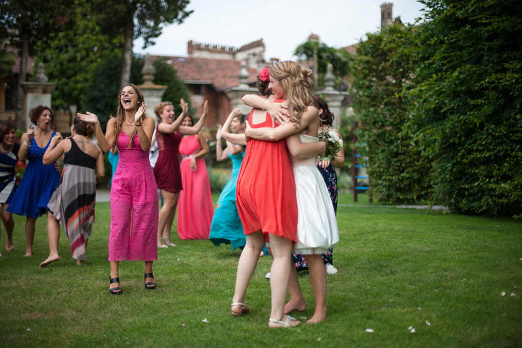 Fotografia di matrimonio. L'abbraccio della sposa con le amiche. Foto di Luca Finessi.