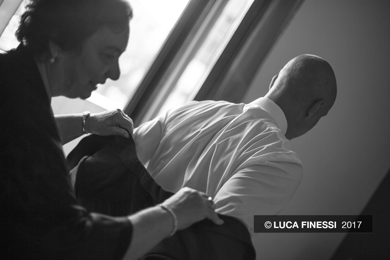 Fotografia di matrimonio. Foto in bianco e nero dello sposo mentre indossa la giacca. Foto di Luca Finessi.